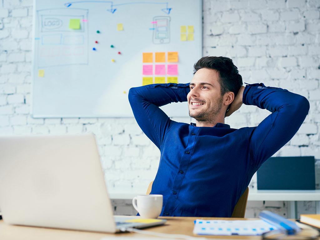 Mann am Schreibtisch lehnt sich zurück und sieht zufrieden aus