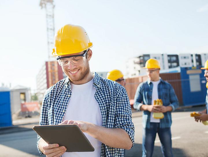 Ein Mann erfasst auf einer Baustelle Daten mit dem Tablet