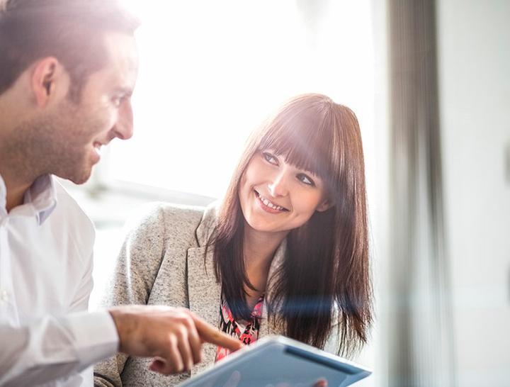 Ein Kollege ist im Gespräch mit seiner Kollegin und zeigt ihr etwas auf seinem Tablet